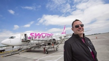 Steven Greenway, President and CEO of Swoop Airlines, poses for a photo in front of one of their Boeing 737 planes on display during a media event, Tuesday, June 19, 2018 at John C. Munro International Airport in Hamilton, Ontario. THE CANADIAN PRESS/Tara Walton