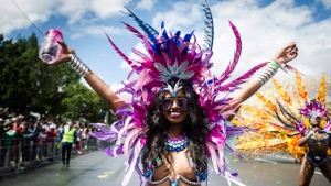 A parade participant performs during the Grand Parade at the Caribbean Carnival in Toronto on Saturday, August 5, 2017. (THE CANADIAN PRESS/Christopher Katsarov)