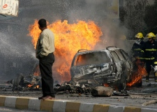 Iraqi fire fighters extinguish a fire following a car bomb explosion in Baghdad, Iraq on Dec. 7, 2006. (AP / Hadi Mizban)