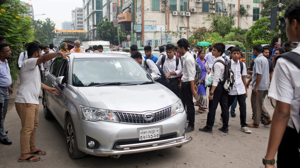Bangladeshi students stop a car to check its license as they block a road during a protest in Dhaka, Bangladesh, Saturday, Aug. 4, 2018. Five days of protests by tens of thousands of students angry over the traffic deaths of two of their colleagues have largely cut off the capital Dhaka from the rest of Bangladesh, as the demonstrators pressed their demand for safer roads. (AP Photo/A. M. Ahad)