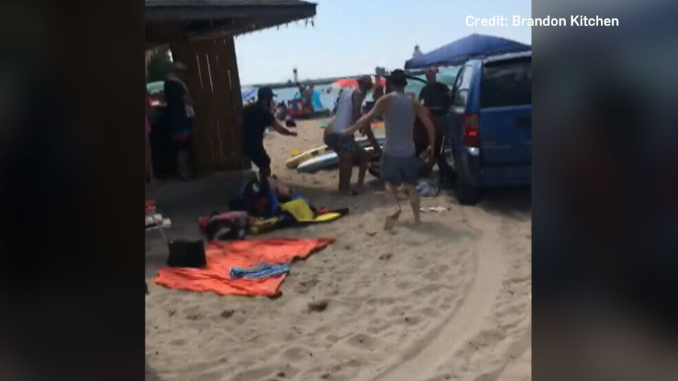 A still from video posted by Brandon Kitchen shows bystanders pulling a man out of a minivan that drove onto the beach in Port Dover, Ont., on Sunday, August 4, 2018.