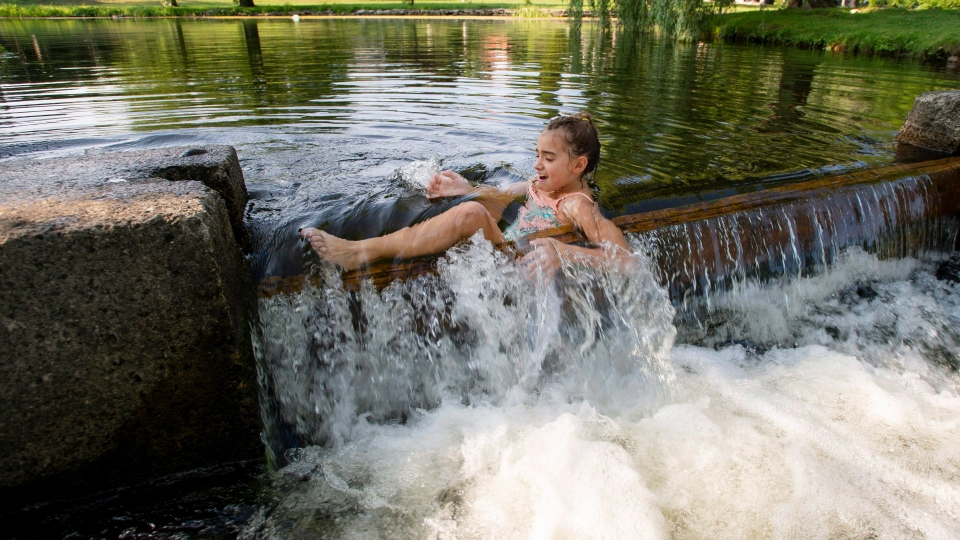 Tahia Mosher, 6, cools off in the Tay River in Stewart Park in Perth, Ont., on Sunday, Aug. 5, 2018. (THE CANADIAN PRESS / Justin Tang)