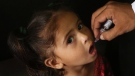 A Pakistani health worker gives a polio vaccine to a girl in a passenger train, in Karachi, Pakistan, Monday, May 7, 2018. (AP Photo/Fareed Khan)