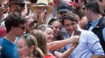 Prime Minister Justin Trudeau, front right, takes a selfie with two women during a visit to B.C. Day celebrations in Penticton, B.C., on Monday August 6, 2018. (Darryl Dyck / THE CANADIAN PRESS)