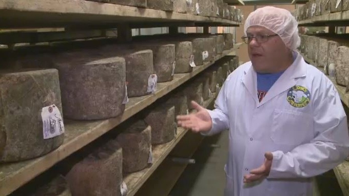 Cheesemaker Armand Bernard shows off wheels of Avonlea clothbound cheddar at the Cows Creamery in Charlottetown.