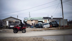 A man rides his ATV in the northern Ontario First Nations reserve in Attawapiskat, Ont., on Tuesday, April 19, 2016. THE CANADIAN PRESS/Nathan Denette