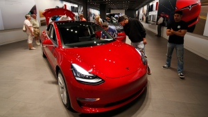 Prospective customers confer with sales associates as a Model 3 sits on display in a Tesla showroom in the Cherry Creek Mall in Denver, July 6, 2018. (AP Photo/David Zalubowski)