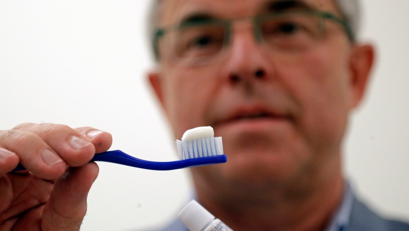 Philippe Hujoel, a dentist and University of Washington professor, holds a toothbrush and toothpaste as he poses for a photo in an office at the school in Seattle on Friday, Aug. 3, 2018. (Elaine Thompson / The Associated Press)
