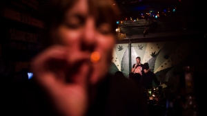 Comedian Phil Luzi performs while Joanne Baker smokes a joint at the Underground Comedy & Social Club, a marijuan-friendly comedy club in Toronto, on Friday, August 3, 2018. (THE CANADIAN PRESS / Christopher Katsarov)