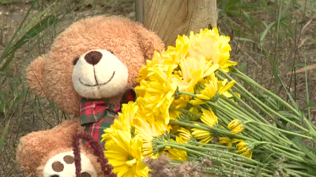 A teddy bear and flowers are seen at Pinery Provincial Park, in memory of the three year old girl.