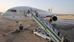 Passengers disembark from a plane belonging to Saudia airline, at Baghdad International Airport, in Iraq, Thursday, Oct. 19, 2017. The rift between the federal government and Saudi Arabia has prompted the country's state airline to suspend operations in Canada. THE CANADIAN PRESS/AP/Karim Kadim