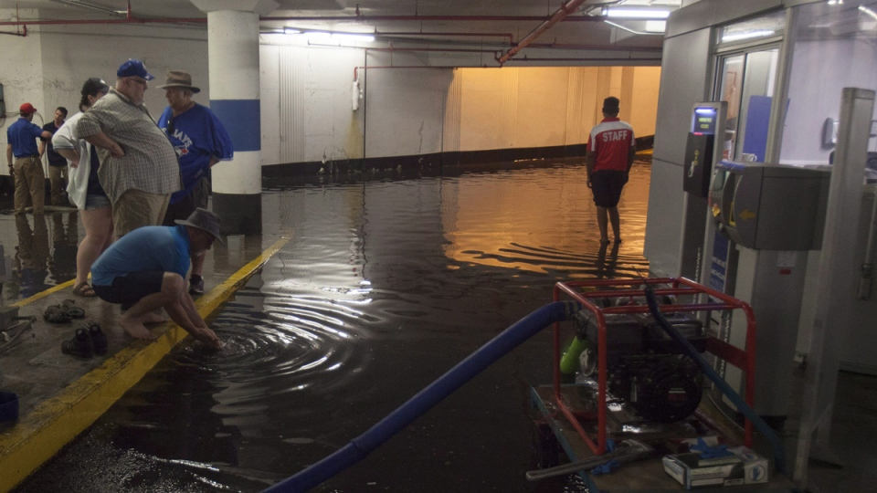 Toronto Blue Jays fans get stuck in the Rogers Centre as the entrance to the parking garage floods with torrential rain, in Toronto on August 7, 2018. (Fred Thornhill / THE CANADIAN PRESS)
