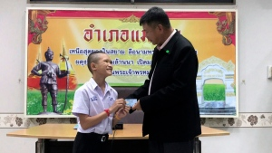 In this release by Chiang Rai Public Relations Office, Mongkol Boonpiam, left, receives an identity card denoting Thai citizenship from Somsak Kunkam Sheriff of Mae Sai during a ceremony in Mae Sai district, Chiang Rai province, northern Thailand, Wednesday, Aug. 8, 2018. (Chiang Rai Public Relations Office via AP)