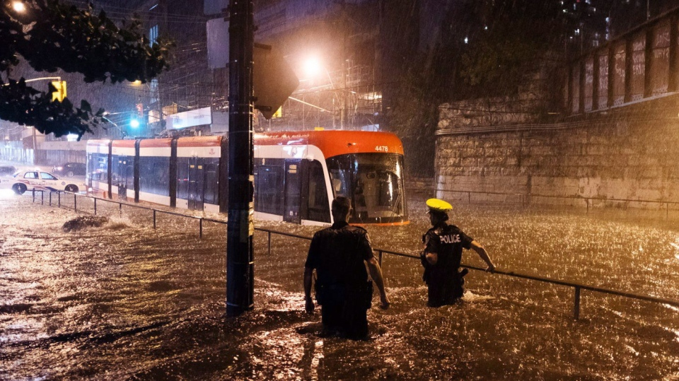 Police officers look on as water floods King St. W. during heavy rain, stopping a streetcar in Toronto on Tuesday, August 7, 2018. THE CANADIAN PRESS/Shlomi Amiga
