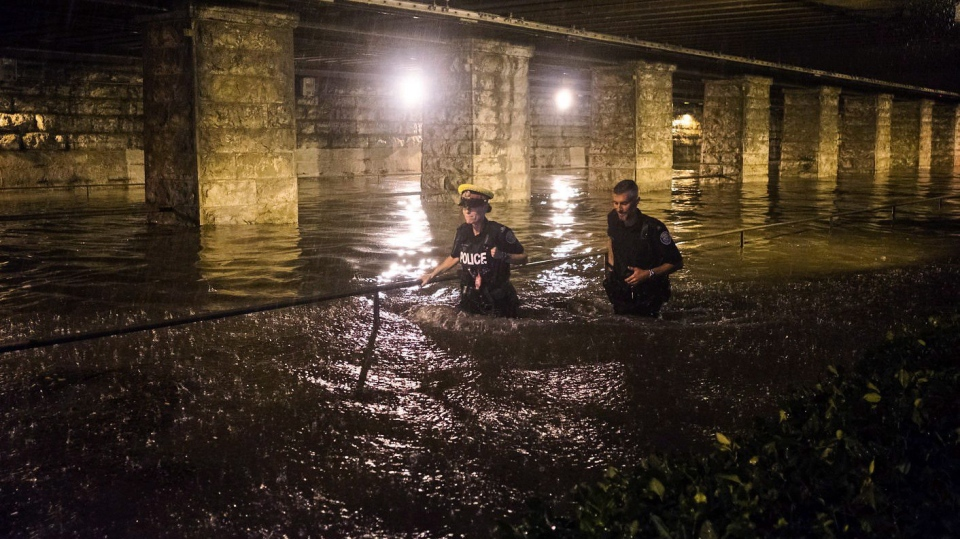 Police officers wade through water flooding an underpass on King St. W. during heavy rain in Toronto on Tuesday, August 7, 2018. THE CANADIAN PRESS/Shlomi Amiga