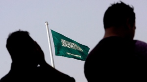 People pray at an open air makeshift mosque in front of a giant Saudi Flag in Jiddah, Saudi Arabia, Wednesday, June 21, 2017. THE CANADIAN PRESS / AP, Amr Nabil