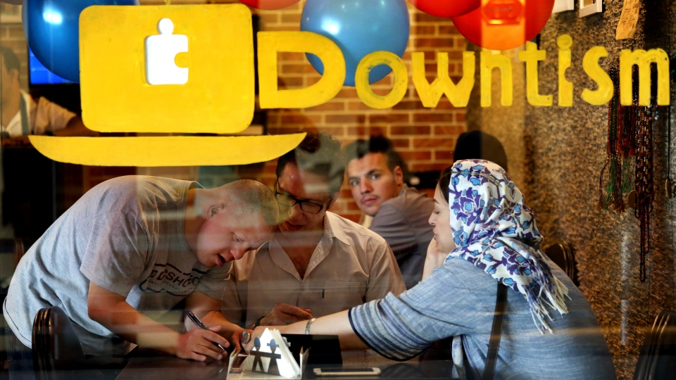 In this Monday, Aug. 6, 2018 photo, cafe staffer Ali Bakhti, with down syndrome, left, takes order in Downtism Cafe in Tehran, Iran. (AP Photo/Ebrahim Noroozi)