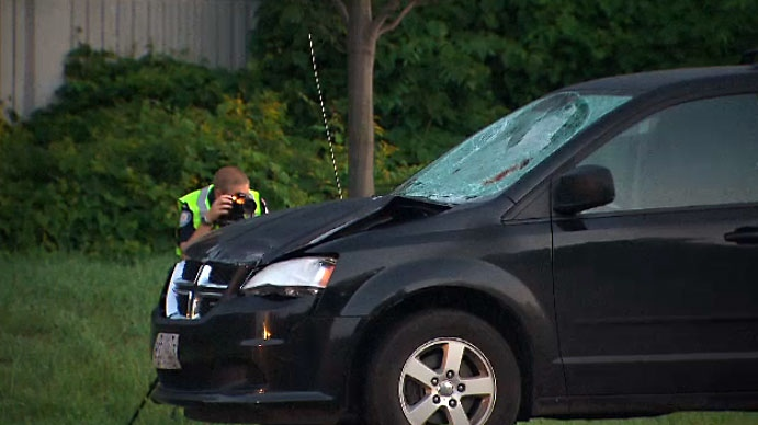 A Toronto police investigator photographs one of two vehicles involved in a fatal pedestrian crash in Port Union on August 9, 2018.