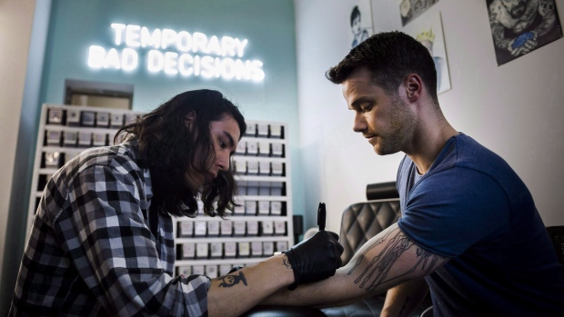 5ce2c2503 Jamie Gillingham, right, receives a semi-permanent tattoo at Inkbox in  Toronto on Monday, July 23, 2018. (Christopher Katsarov/ The Canadian Press)