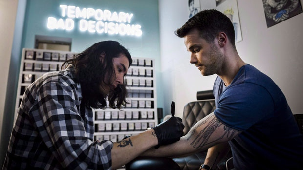 Jamie Gillingham, right, receives a semi-permanent tattoo at Inkbox in Toronto on Monday, July 23, 2018. (THE CANADIAN PRESS/Christopher Katsarov)