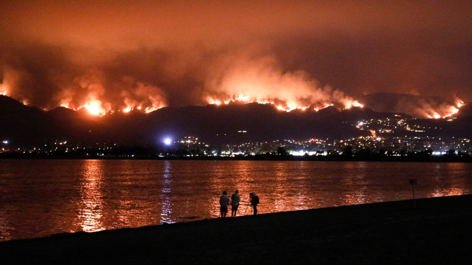 Onlookers are silhouetted against the reflection of a wildfire burning in the Cleveland National Forest in Lake Elsinore, Calif., Wednesday, Aug. 8, 2018. (AP Photo/Jae C. Hong)