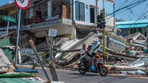 In this file photo, motorists ride past buildings ruined by Sunday's earthquake in Pamenang, Lombok Island, Indonesia, Friday, Aug. 10, 2018. (AP Photo/Fauzy Chaniago)