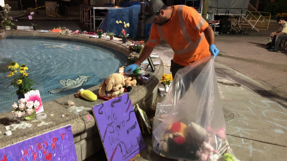 A city worker packs up some of the flowers and other artifacts left at a makeshift memorial to the Danforth shooting victims early Friday morning. (Peter Muscat)