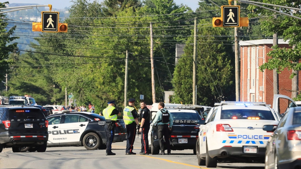 Police officers survey the area of a shooting in Fredericton, N.B. on Friday, August 10, 2018. THE CANADIAN PRESS/Keith Minchin
