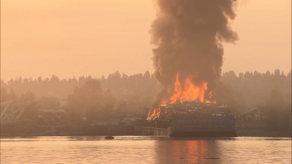 A barge full of crushed cars burns near the Pattullo Bridge on the Surrey, B.C. side.