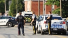 Police and RCMP officers survey the area of a shooting in Fredericton, N.B. on Friday, August 10, 2018. (THE CANADIAN PRESS/Keith Minchin)