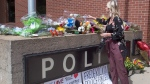 Flowers are placed outside the police station in Fredericton on Friday, Aug. 10, 2018. THE CANADIAN PRESS/Andrew Vaughan