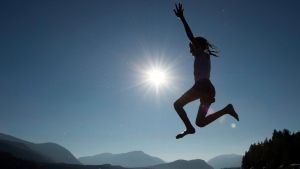 A young girl is silhouetted against the sun as she jumps in the waters of Sproat Lake in Port Alberni, B.C. (THE CANADIAN PRESS/Jonathan Hayward)