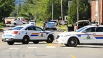 Police and RCMP officers survey the area of a shooting in Fredericton, N.B. on Friday, August 10, 2018. THE CANADIAN PRESS/Keith Minchin