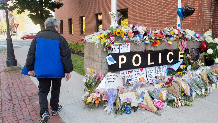 A resident views the makeshift tribute outside the police station in Fredericton on Saturday, Aug. 11, 2018. Two city police officers were among four people who died in a shooting in a residential area on the city's north side. THE CANADIAN PRESS/Andrew Vaughan