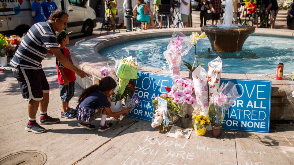People leave flowers at a memorial honouring the victims of a shooting on Sunday evening on Danforth, Avenue in Toronto on Tuesday, July 24, 2018. THE CANADIAN PRESS/Mark Blinch