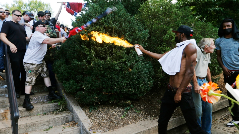 In this Aug. 12, 2017, file photo, a counter demonstrator uses a lighted spray can against a white nationalist demonstrator at the entrance to Lee Park in Charlottesville, Va. (AP Photo/Steve Helber, File)