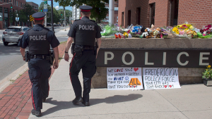 Two officers walk past an array of flowers outside the police station in Fredericton on Friday, Aug. 10, 2018.THE CANADIAN PRESS/Andrew Vaughan