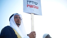 """An Arab Israeli man holds a sign that reads """""""