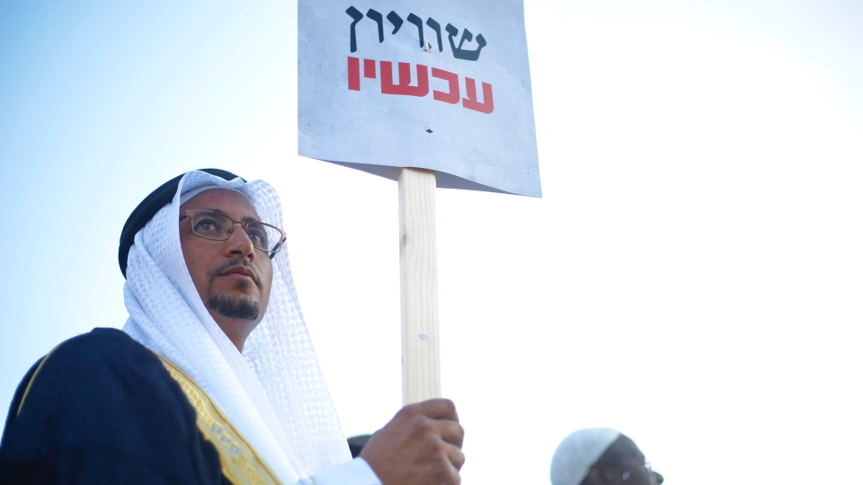 """An Arab Israeli man holds a sign that reads """"Equality now"""" during a protest against the Jewish nation bill in Tel Aviv, Israel, Saturday, Aug. 11, 2018. (AP Photo/Ariel Schalit)"""