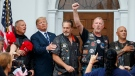 U.S. President Donald Trump stands in the rain with members of Bikers for Trump and supporters after saying the Pledge of Allegiance, Saturday, Aug. 11, 2018, at the clubhouse of Trump National Golf Club in Bedminster, N.J. (AP Photo/Carolyn Kaster)