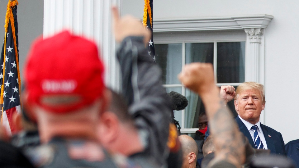 U.S. President Donald Trump meets members of Bikers for Trump and supporters, Saturday, Aug. 11, 2018, outside the clubhouse of Trump National Golf Club in Bedminster, N.J. (AP Photo/Carolyn Kaster)
