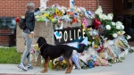 Flowers are placed on a makeshift memorial outside the police station in Fredericton on Saturday, Aug. 11, 2018. (THE CANADIAN PRESS/Andrew Vaughan)