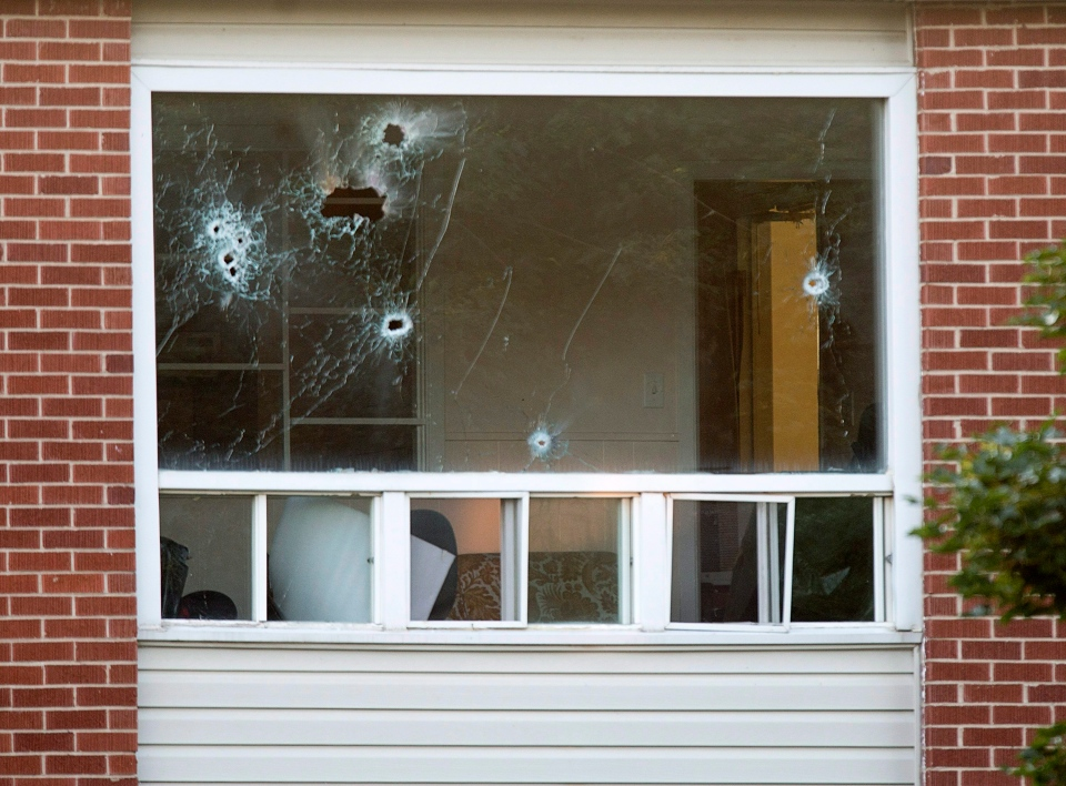 Bullet holes riddle a window in an apartment building in Fredericton on Friday, Aug. 10, 2018. (THE CANADIAN PRESS/Andrew Vaughan)