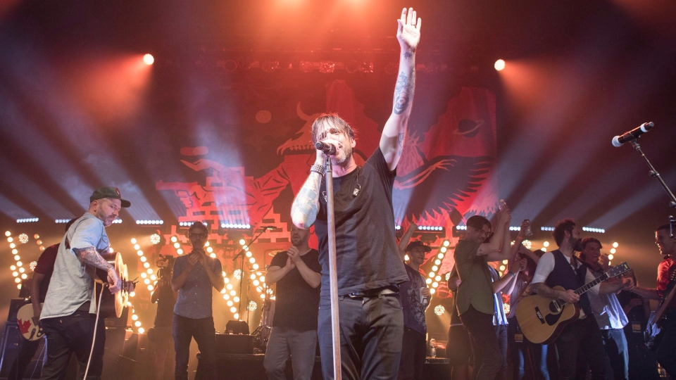 Benjamin Kowalewicz, the lead singer of Billy Talent, stands on stage with other guest performers as they thank the crowd at the Danforth Music Hall, in Toronto on Saturday, Aug. 11, 2018, as part of a benefit concert organized by the band to raise money for the victims of the Danforth shooting. (THE CANADIAN PRESS / Chris Young)