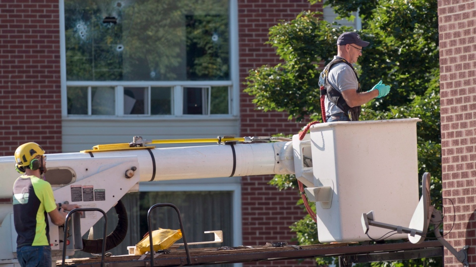 An RCMP forensic investigator prepares to examine a building adjacent to where Matthew Vincent Raymond is alleged to have gone on a shooting spree in Fredericton on Saturday, August 11, 2018. THE CANADIAN PRESS/Andrew Vaughan