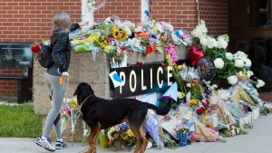 Flowers are placed on a makeshift memorial outside the police station in Fredericton on Saturday, Aug. 11, 2018. Two city police officers were among four people who died in a shooting in a residential area on the city's north side. THE CANADIAN PRESS/Andrew Vaughan