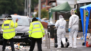 Forensic officers at the scene in the Moss Side area of Manchester, England, where several people have been injured after a shooting, early Sunday Aug. 12, 2018. Police in Manchester say 10 people have been hospitalized as the result of a shooting after a Caribbean carnival in the city. (Peter Byrne / PA via AP)