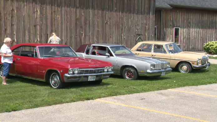 Vintage cars are lined up on grass for display at the memorial car show and rally.
