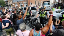 Demonstrators confront police at the intersection where Heather Heyer was killed last year as they mark the anniversary of the Unite the Right rally in Charlottesville, Va., Sunday, Aug. 12, 2018. On that day, white supremacists and counterprotesters clashed in the city streets before a car driven into a crowd struck and killed Heyer. (AP / Steve Helber)