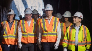 Prime Minister Justin Trudeau, second right, and Minister of Infrastructure and Communities Francois-Philippe Champagne walks through a tunnel as he visits a site for a STM maintenance garage in Montreal on August 9, 2018. (Graham Hughes/ The Canadian Press)